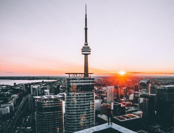Mann steht auf Hochhaus und blickt über die Skyline Torontos in den Sonnenuntergang