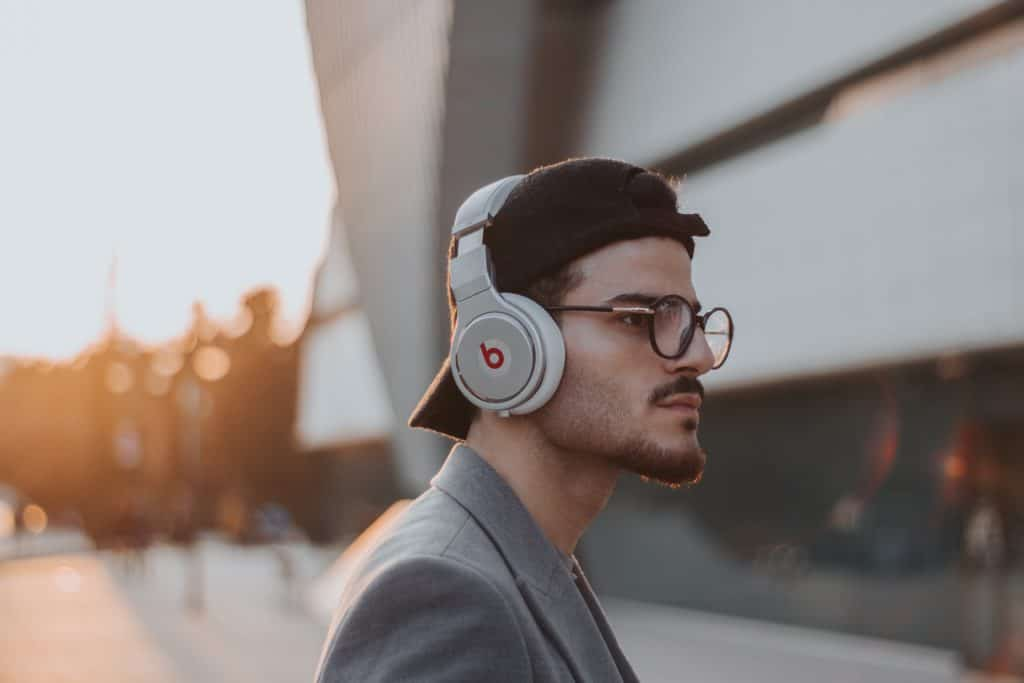 Junger Mann der mit Kopfhörern Musik hört