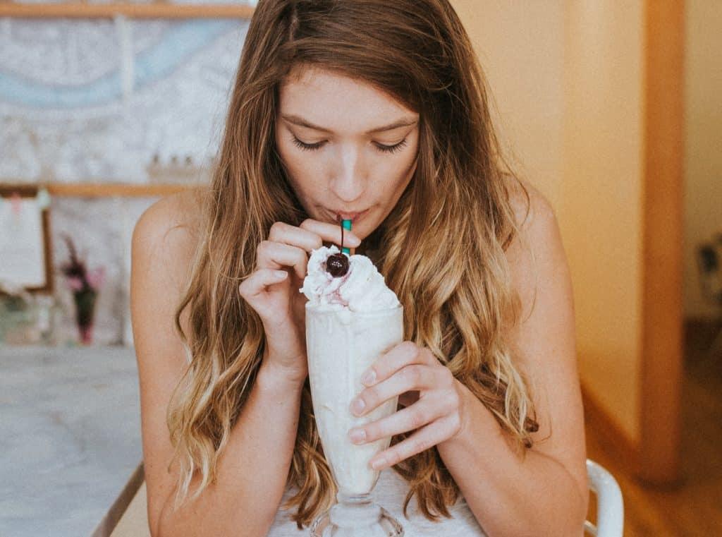Eine junge Frau trinkt einen Milchshake