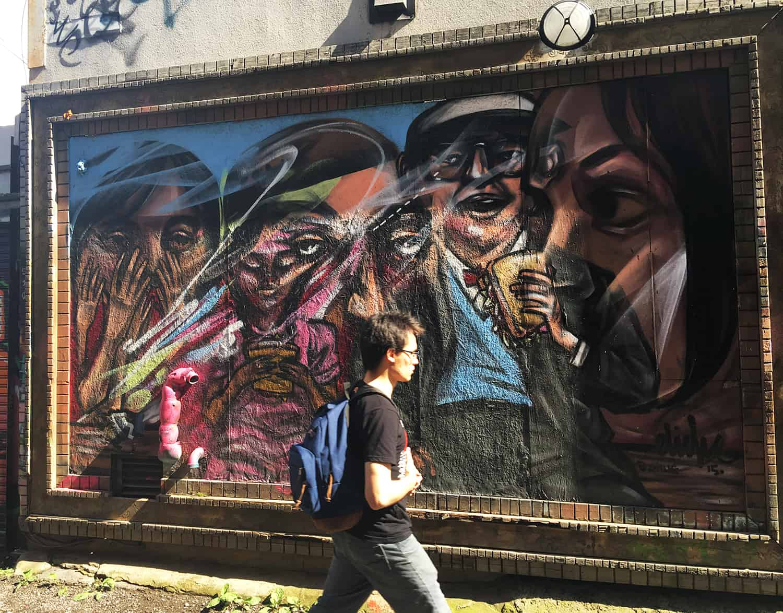 Junger Mann mit Rucksack läuft durch die Graffiti Alley