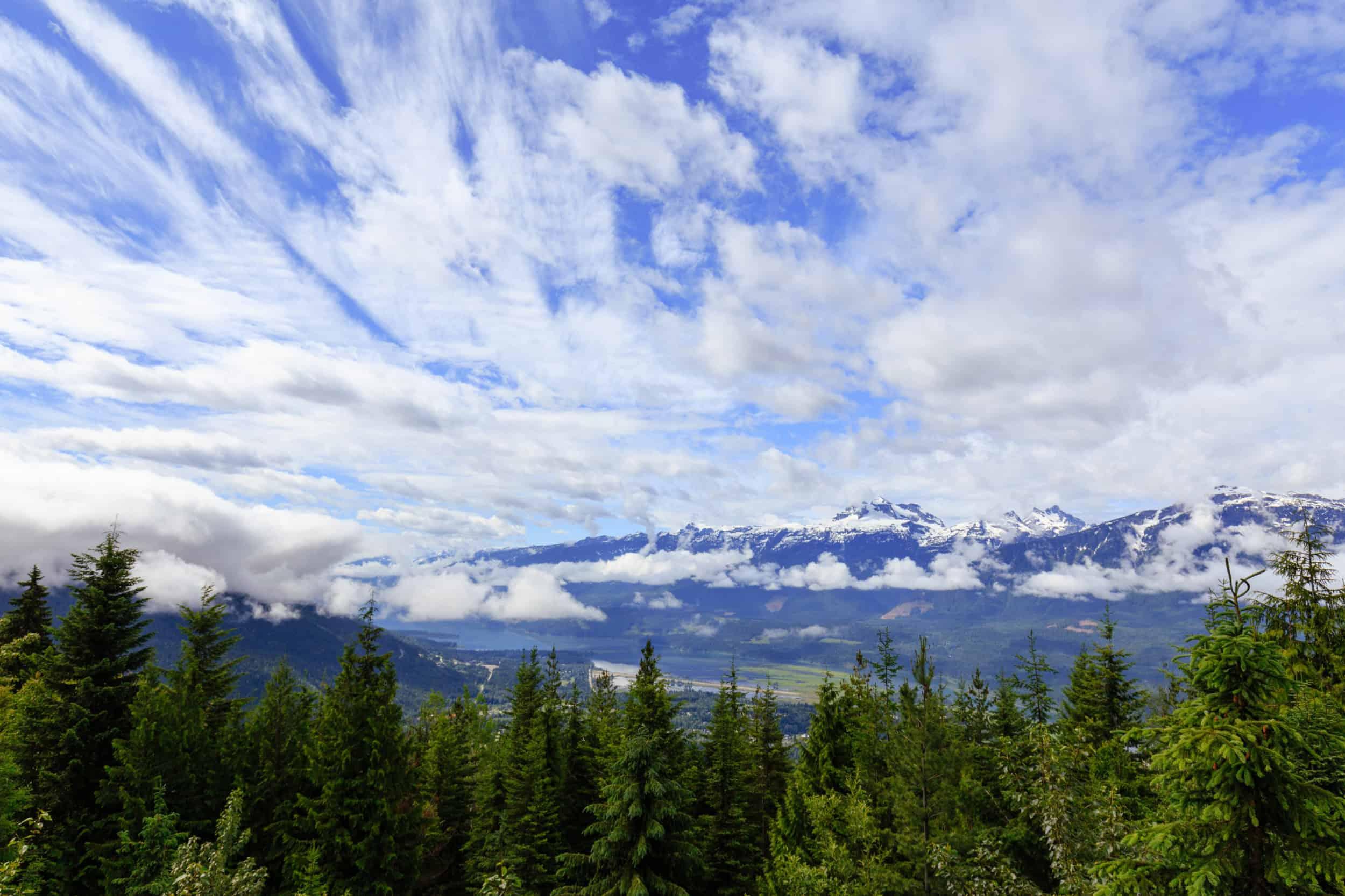 Blauer Himmel über grünen Wäldern eines Nationalparks in Kanada