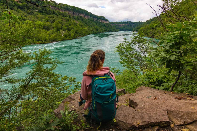 Junge Frau sitzt mit dem Rücken zum Betrachter an einem Flussufer