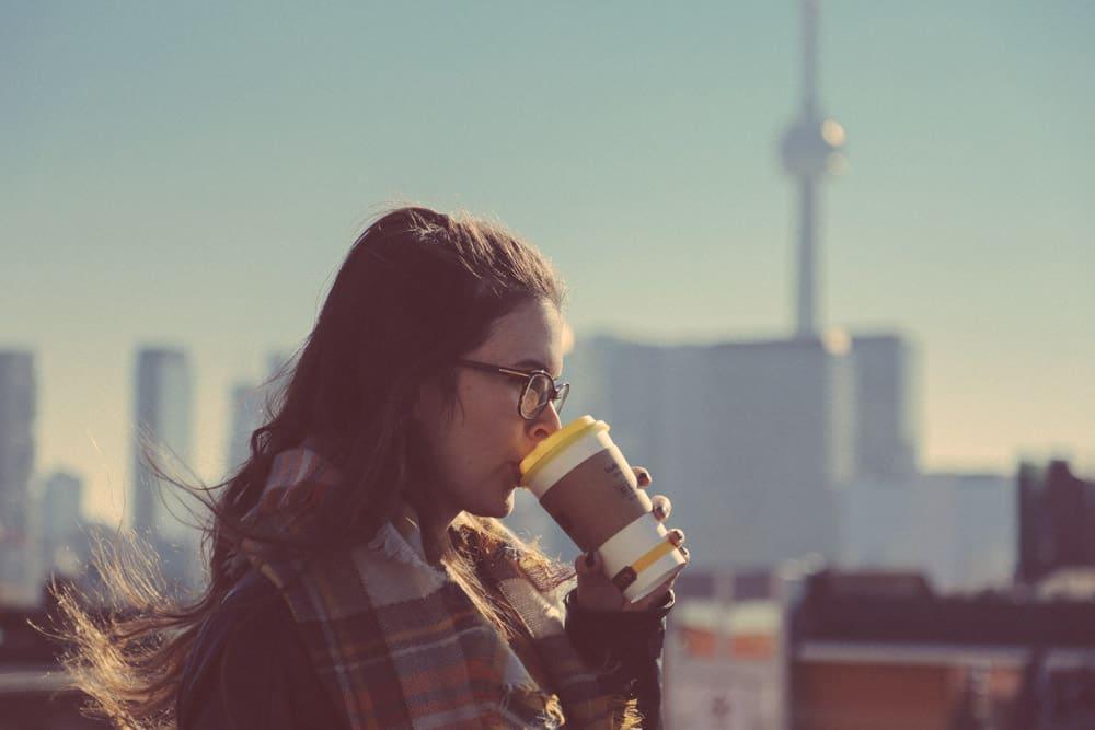 junge Frau mit Kaffe in der Hand, CN Tower im Hintergrund