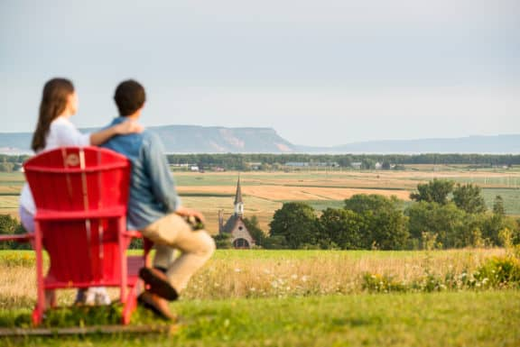 Besucher auf roten Stühlen am Grand-Pré Park. Eine UNESCO Weltkulturerbe.