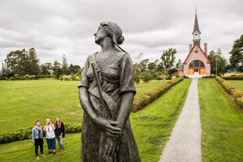Besucher bestaunen die Evangeline Statue in den Victorian Gardens, mit der Memorial Church im Hintergrund.