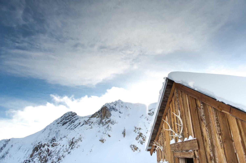 verschneite Berghütte mit Geweih über dem Eingang