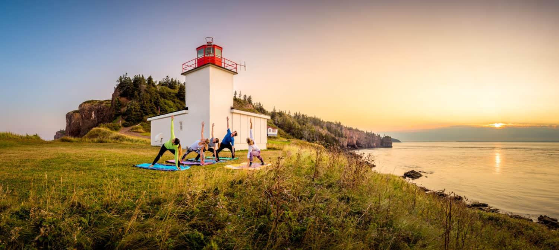 Yoga bei Sonnenuntergang vor Leuchtturm