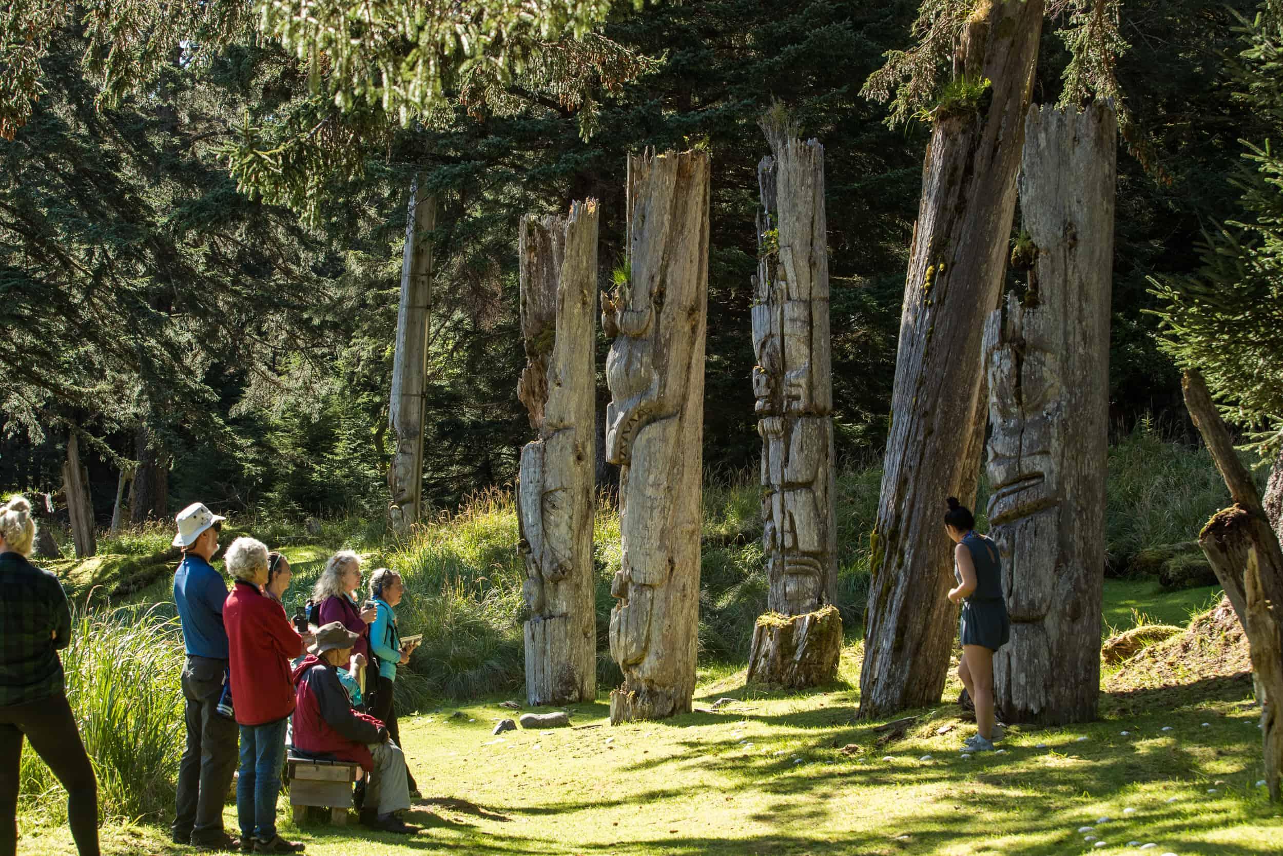 Touristen vor alten Totem