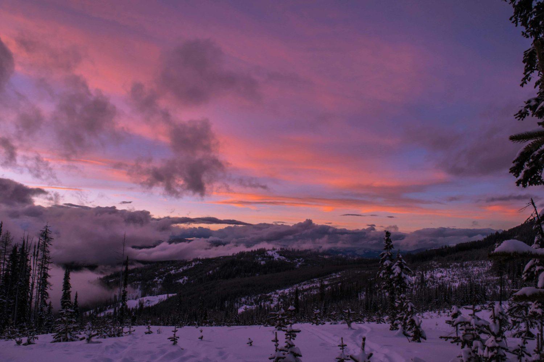 Sonnenuntergang in lila hinter Bergen, die von Wolken bedeckt sind in Rossland