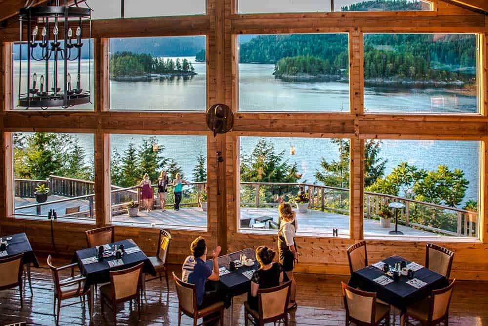 Leute die in der gemütlichen West Coast Wilderness Lodge sitzen mit Ausblick auf Gewässer