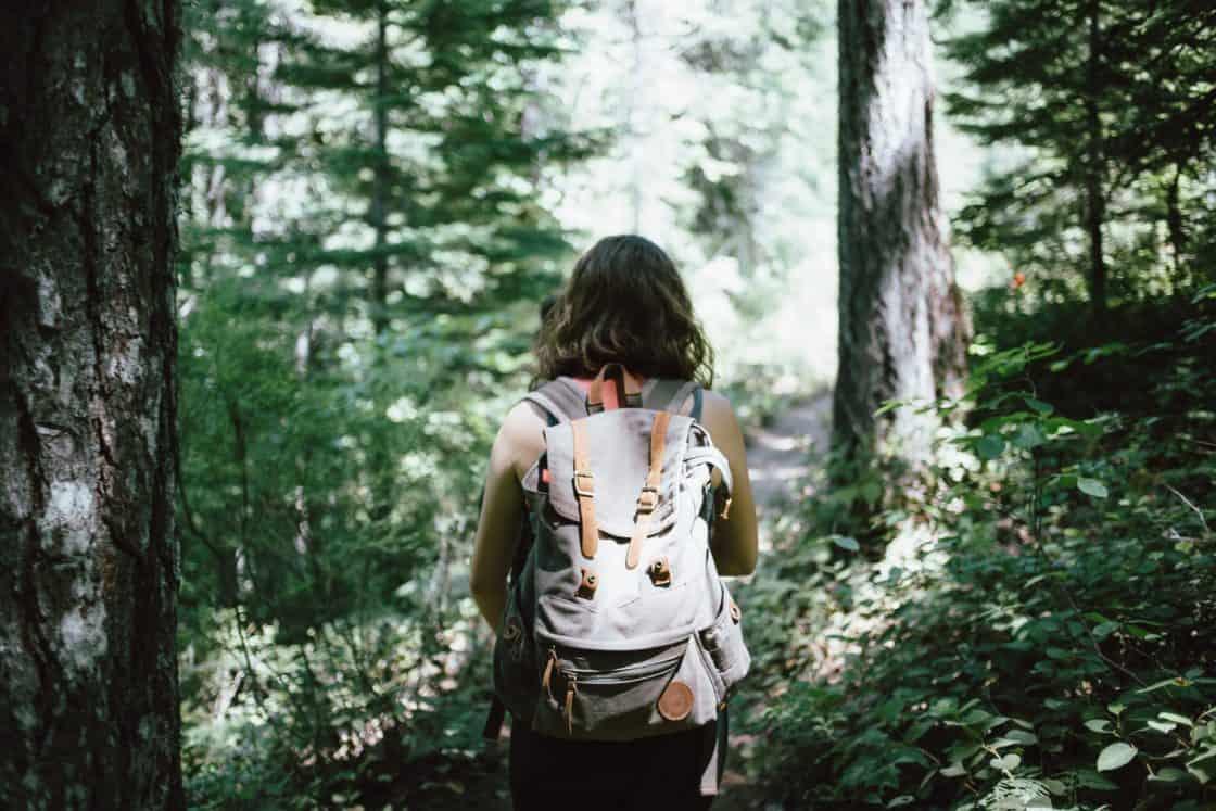 Frau mit Rucksack wandert durch einen Wald