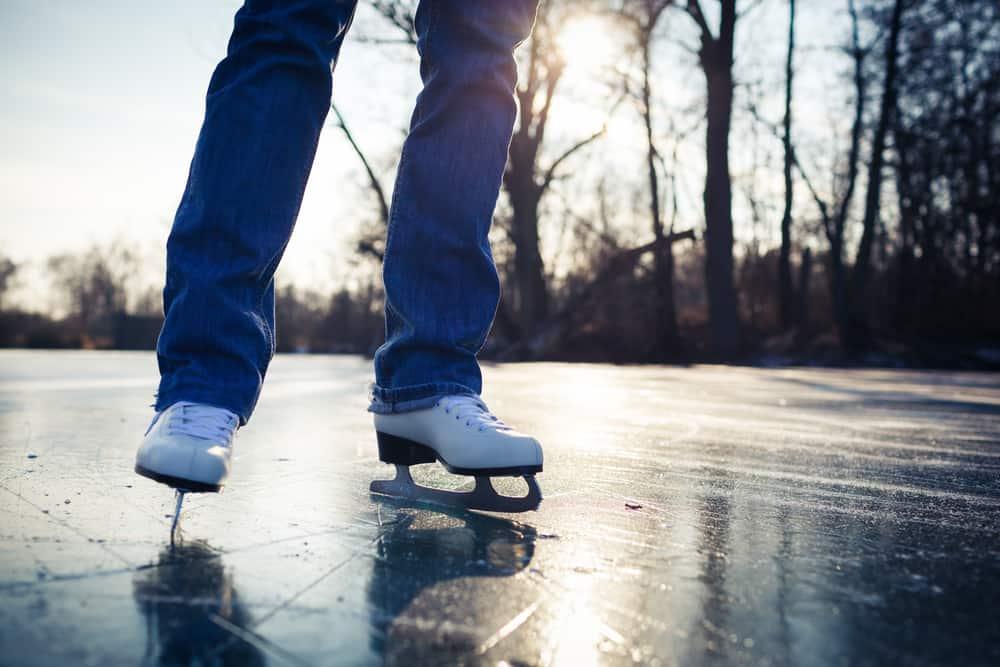 Frau mit weißen Schlittschuhen auf dem Eis