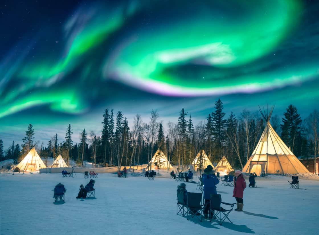 beeindruckende Nordlichter tanzen über den Zelten im Aurora Village in Yellowknife, Kanada.