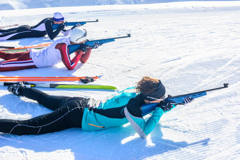 3 Menschen schießen liegend beim Biathlon, Whistler Mountain