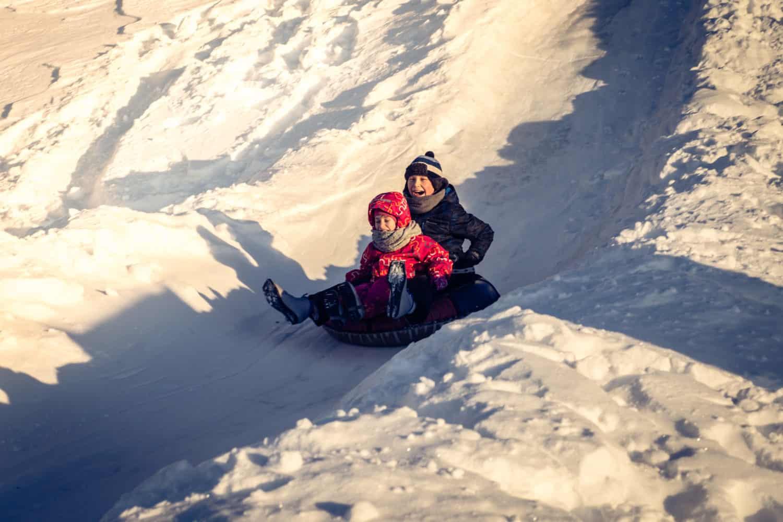 Zwei kleine Kinder rodeln mit einem Reifenschlauch (Tubing) einen Berg hinunter mit freudevollen Gesichtern.