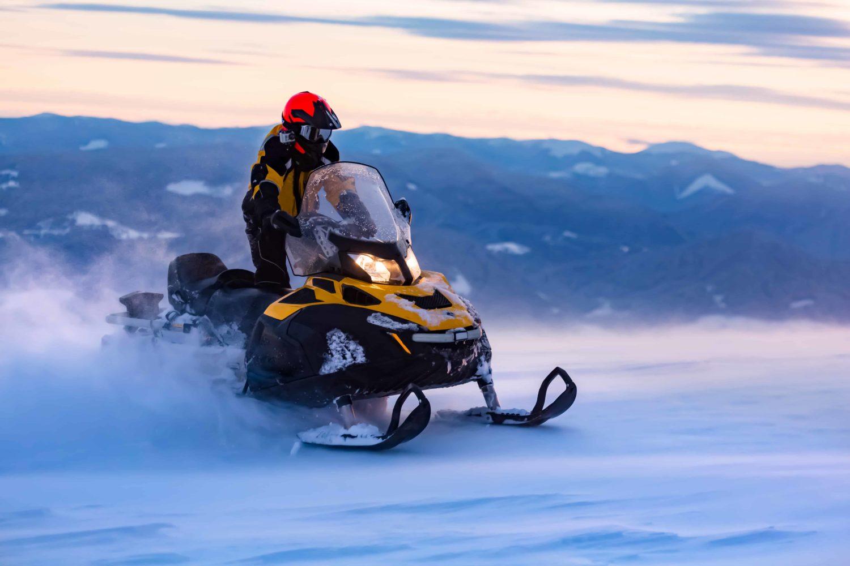 Mann auf Schneemobil bei Sonnenaufgang mit Bergen im Hintergrund