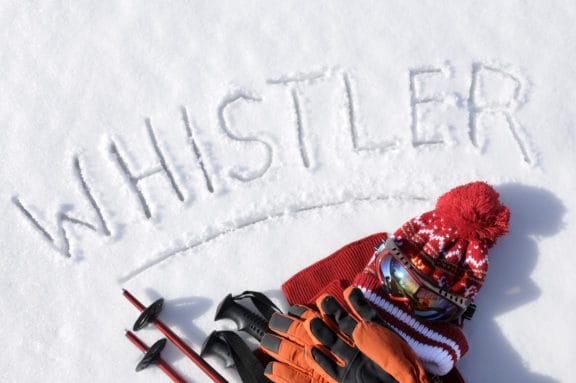 Im Schnee liegende Skisachen. Über den Sachen steht in den schnee geschrieben Whistler