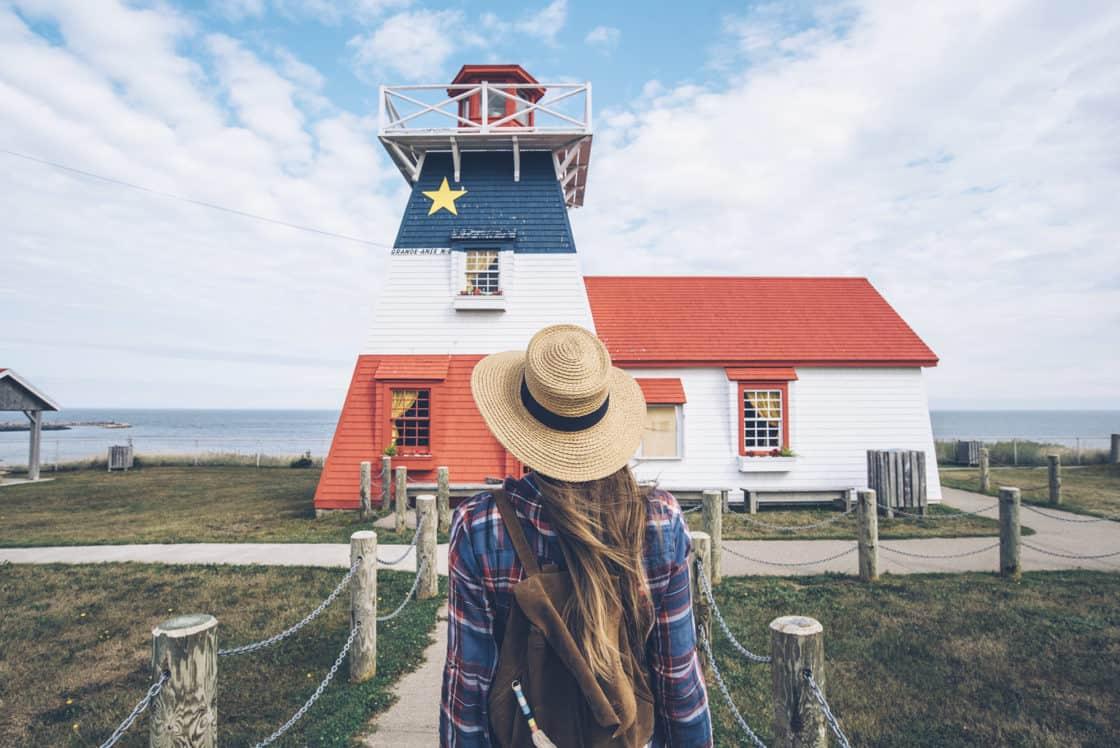Frau vor Leuchtturm mit Acadian Flagge in Grande Anse, New Brunswick