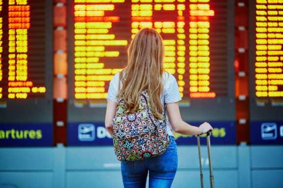 junge Touristin am Flughafen vor Anzeigetafel