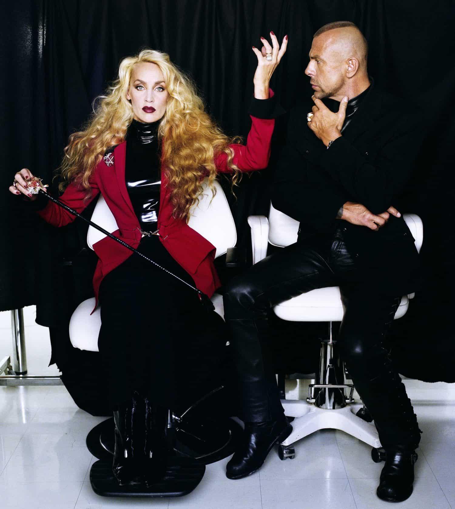 Mann im Sessel schaut auf Frau im Sessel welche eine Pose macht, Kleidung von Thierry Mugler