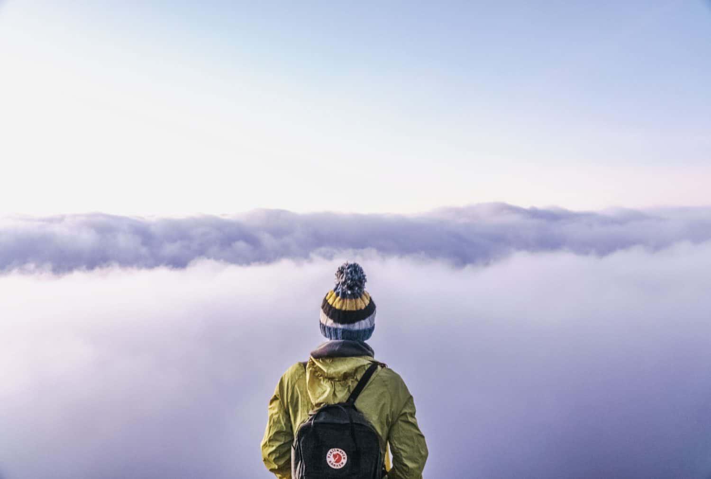 Person mit gelber Jacke steht vor Wolkendecke