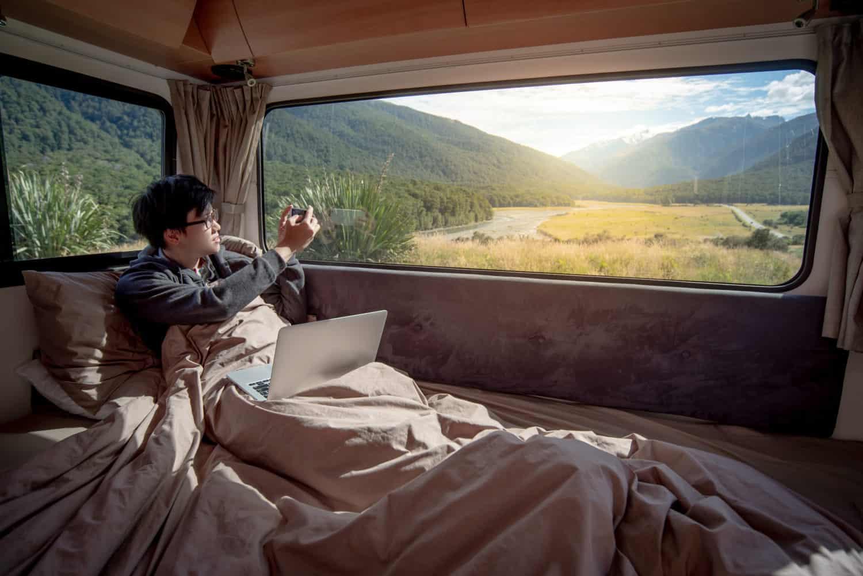 Mann unter Decke macht ein Foto von der Landschaft aus einem Wohnmobil Camper