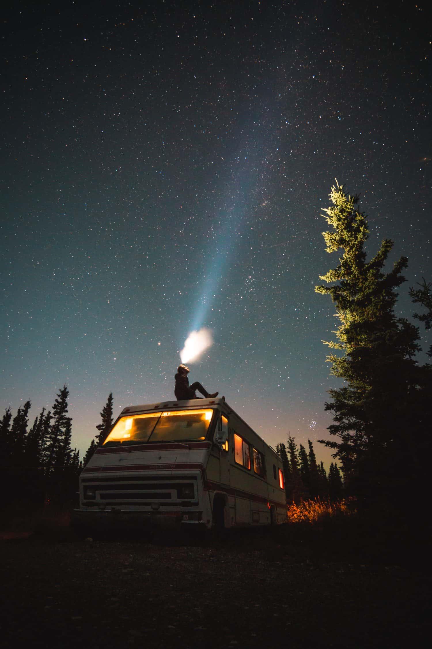 Mann auf Wohnmobil macht ein Foto vom Nachthimmel