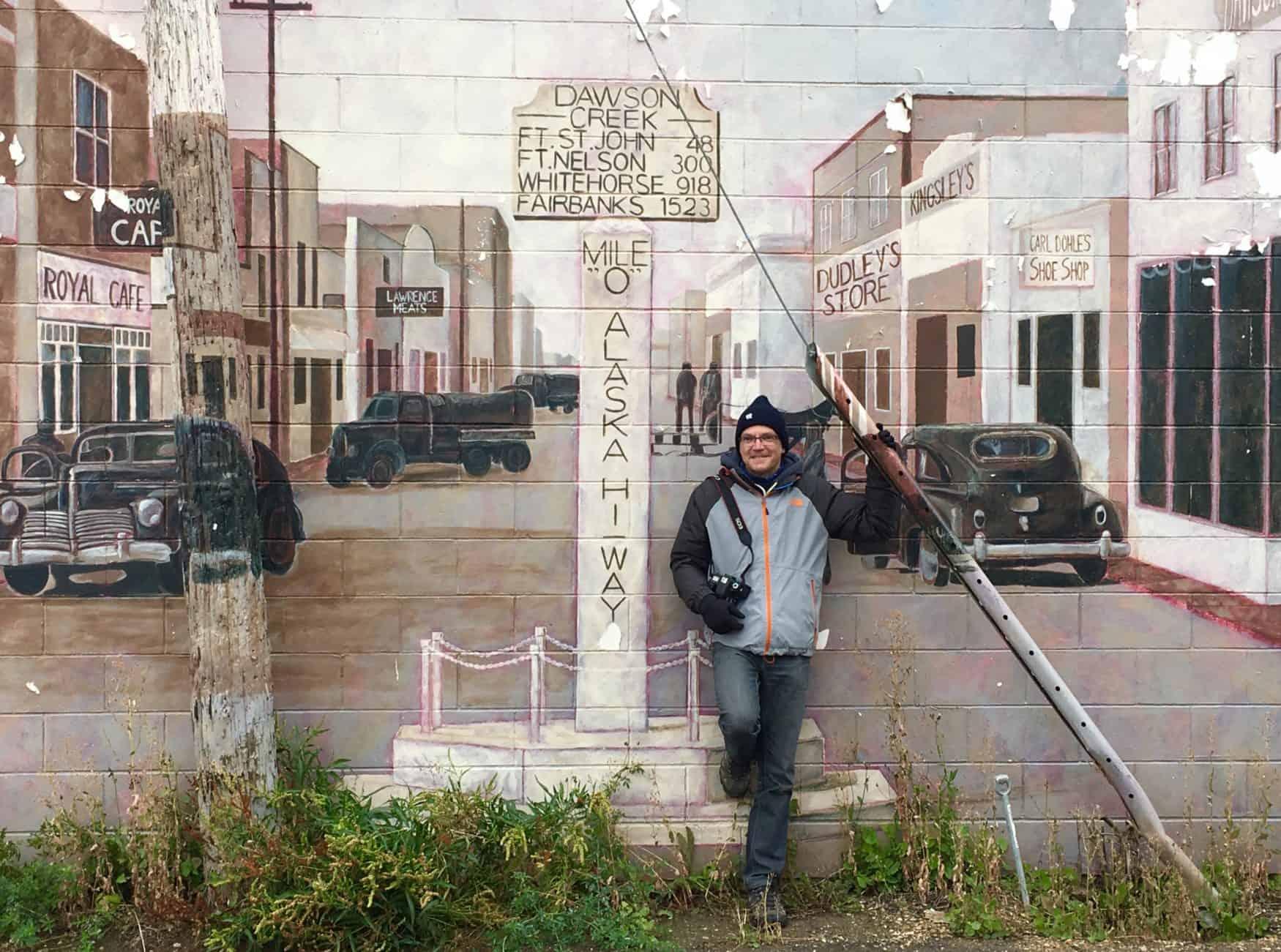 """Vor einem Mural in Dawson Creek. Es zeigt den historischen """"Mile 0"""" Marker des Alaska-Highway."""