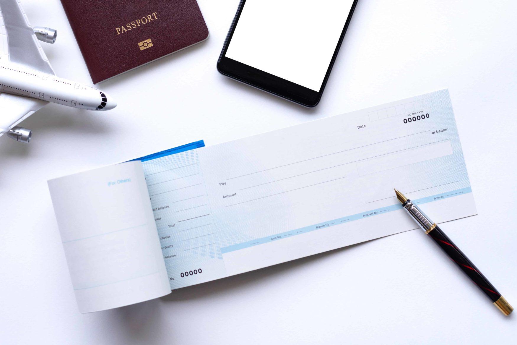 Flugzeug, Scheckbuch, Handy und Pass als Reiseunterlagen