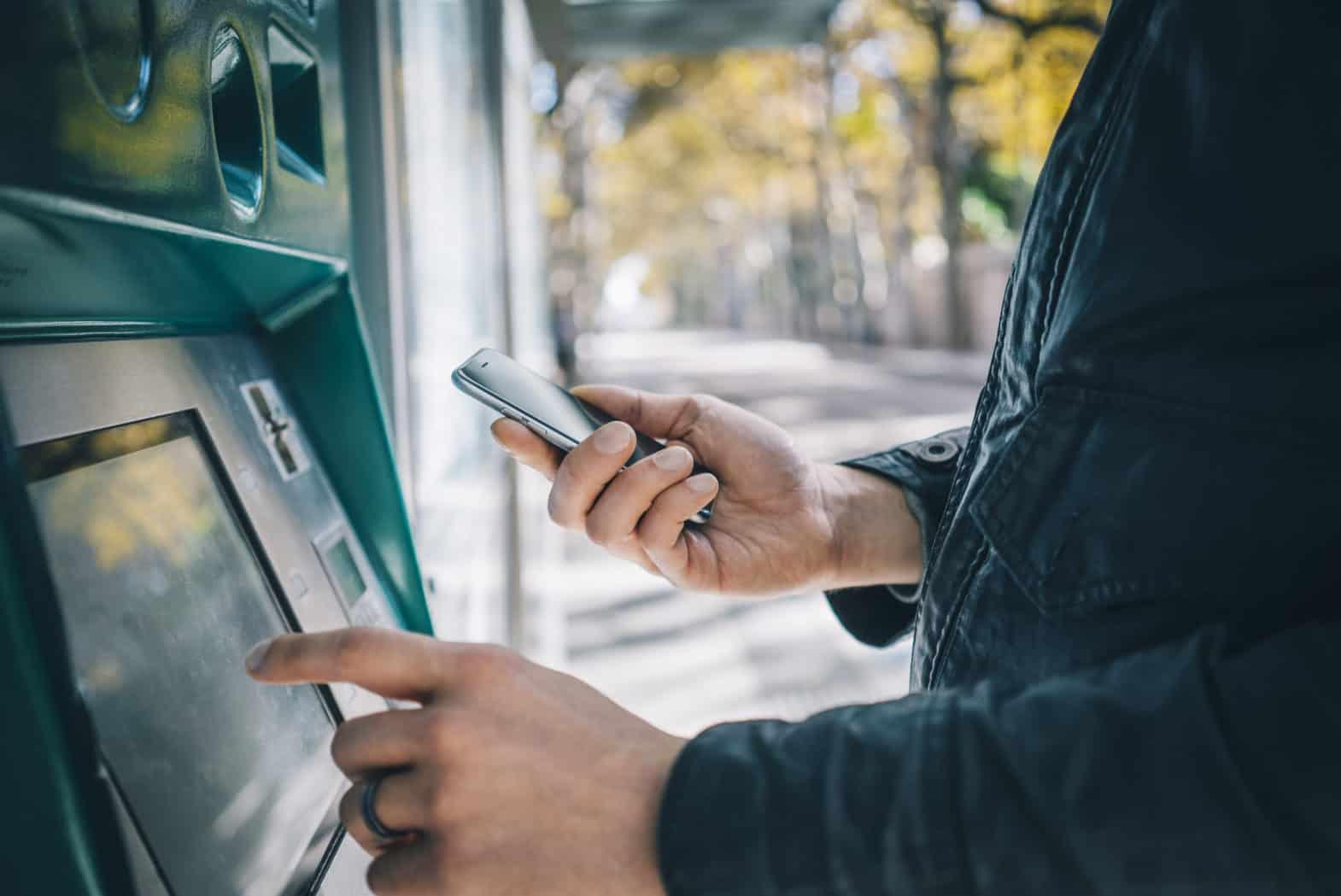 vor einem Bankautomat steht ein Mann der gerade eine Auswahl trifft. Er hat sein Handy in der rechten Hand.