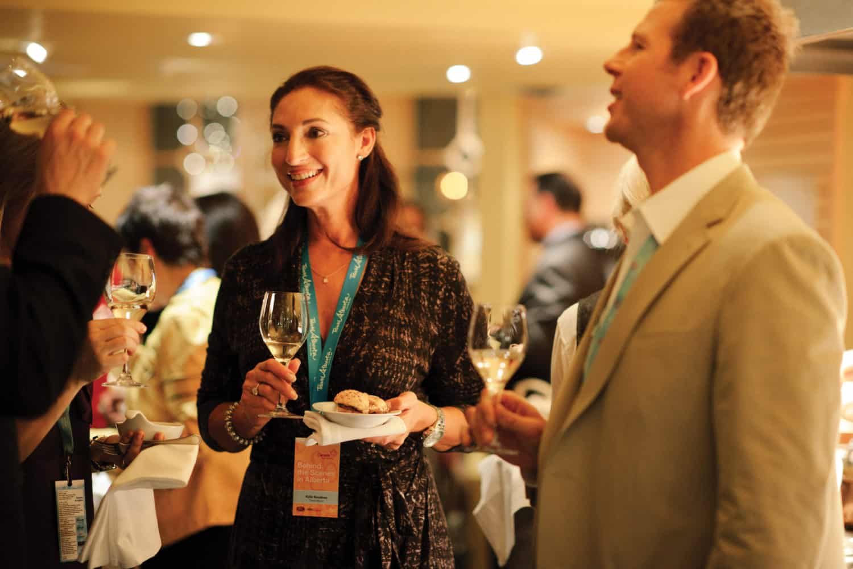 Frau im Fairmont Banff Springs Hotel genießt einen Sekt und etwas zu essen bei einem anregendem Gespräch