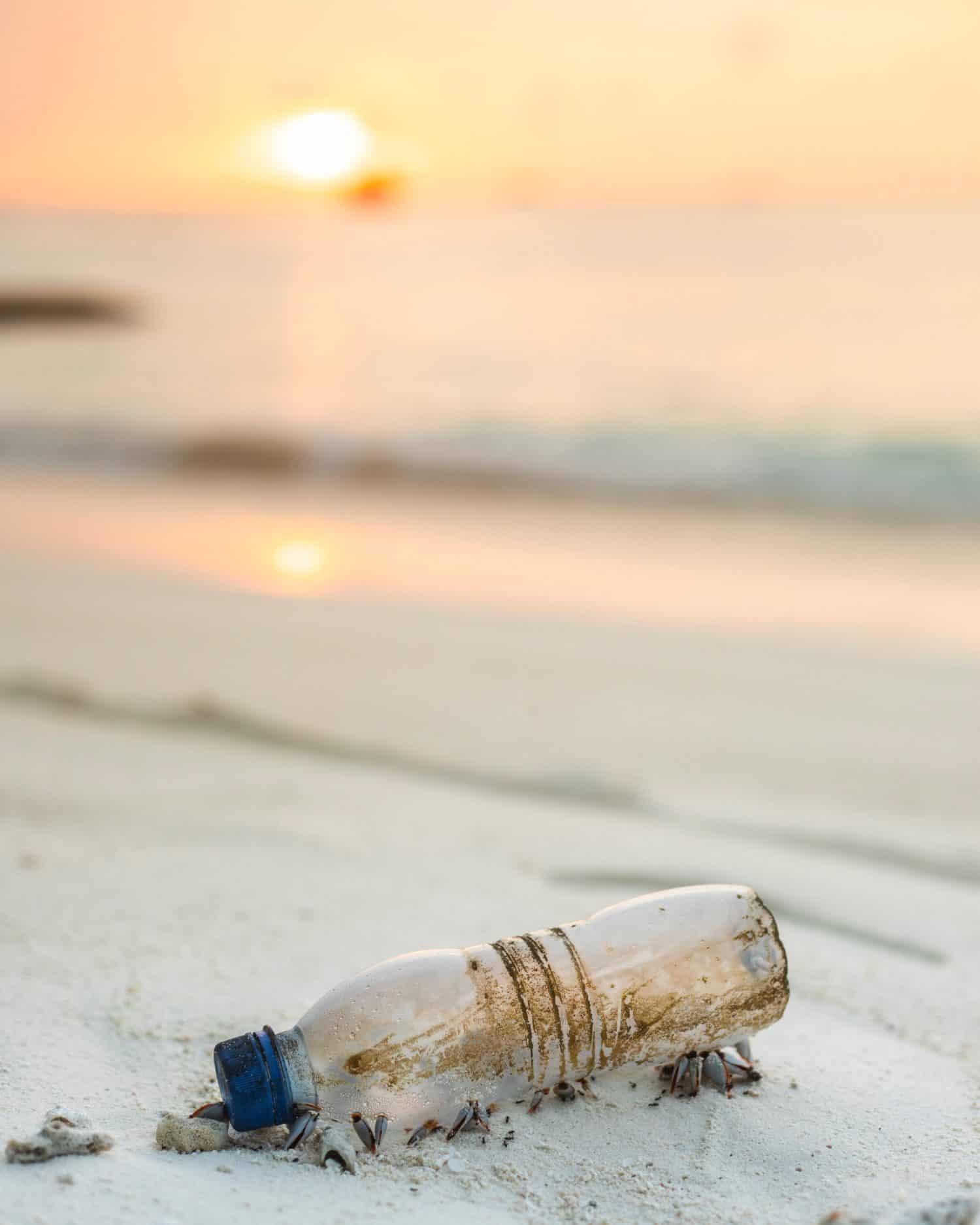 eine Plastikflasche am Strand. Im Hintergrund ist der Sonnenuntergang zu sehen.