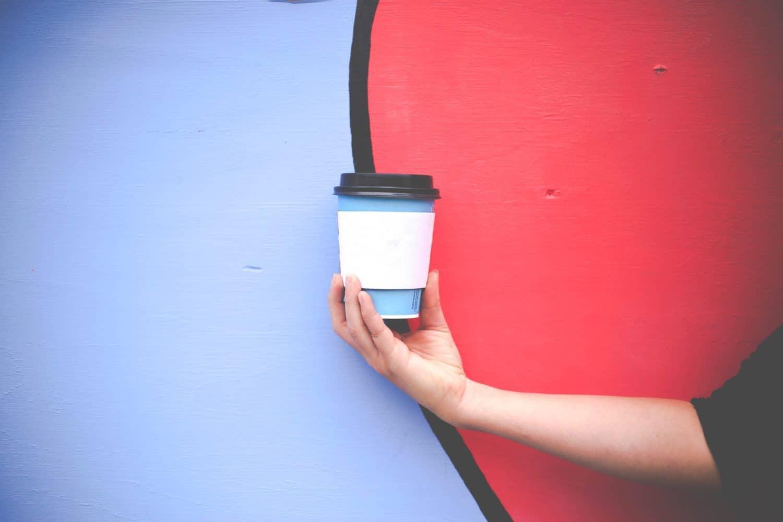 Person hält Styropor to go Kaffee Becher vor einem rot-blauen Hintergrund