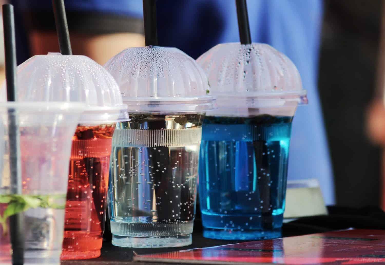 Vier Plastikbecher mit Plastikstrohhalmen stehen hintereinander