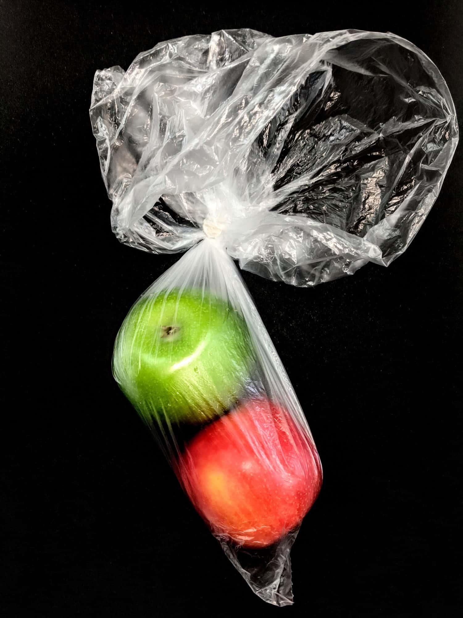 Zwei Äpfel in einer Plastiktüte mit schwarzem Hintergrund