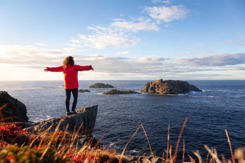Twillingate, Neufundland und Labrador, Kanada. Frau steht auf einem Felsen und streckt die Arme aus. Dahinter ist das Meer.