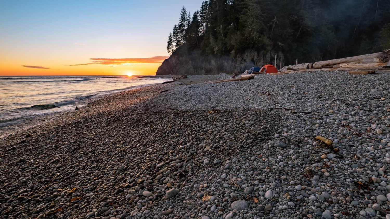West Coast Trail, British Columbia auf Vancouver Island in Kanada. Zelte am Strand mit Felsen im Hintergrung und Sonnenuntergang.