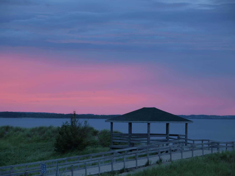 Parlee Beach Provincial Park, Shediac, New Brunswick, Kanada. Vor dem Sonnenuntergang befindet sich ein Parvillion und das Meer im Hintergrund.