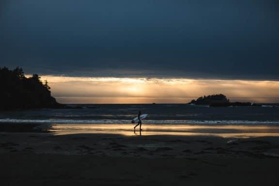 Mann mit Surfboard in der Hand läuft im Sonnenuntergang den Strand in Tofino, Kanada entlang.