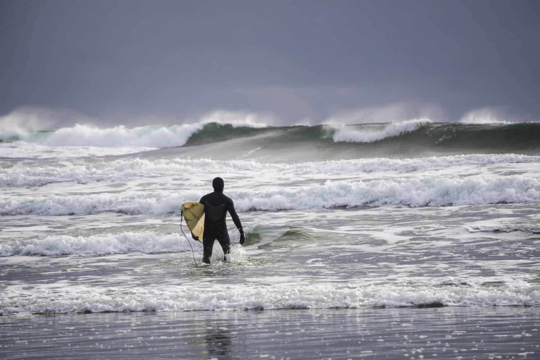 Long Beach, Vancouver Island, B.C., Kanada. Ein Surfer läuft in das Meer am Strand. Natur im Hintergrund.
